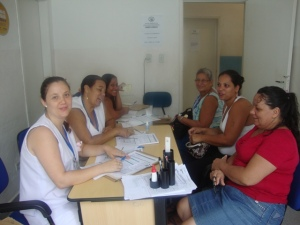 Mulheres preenchem ficha com as técnicas em enfermagem antes de fazer o exame. (Foto: Divulgação)